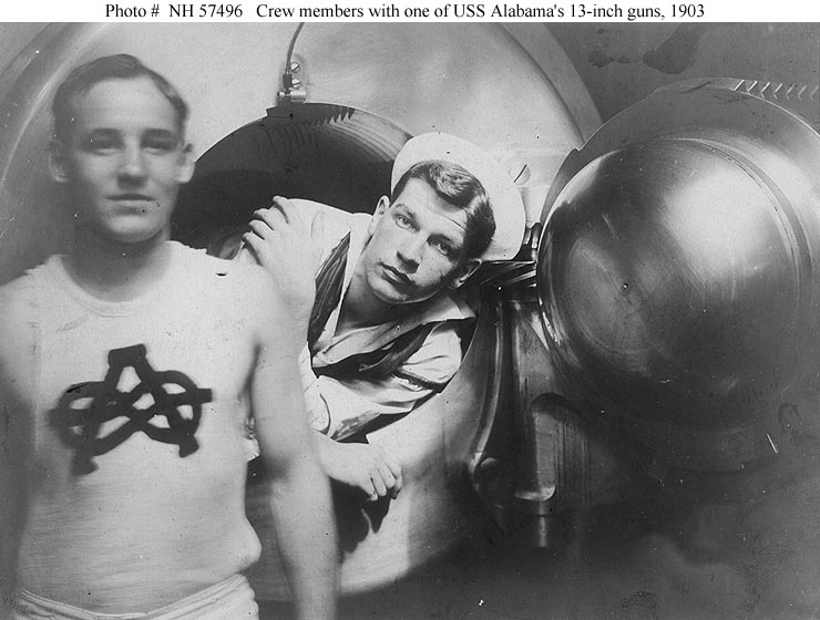 """Crew members F. Petry (left) and W.M. Langridge (in gun) pose at the breech of one of the ship's 13""""/35 guns, 1903. Note the """"A"""" with figure """"8"""" knot on Petry's shirt. Photo # NH 57496"""