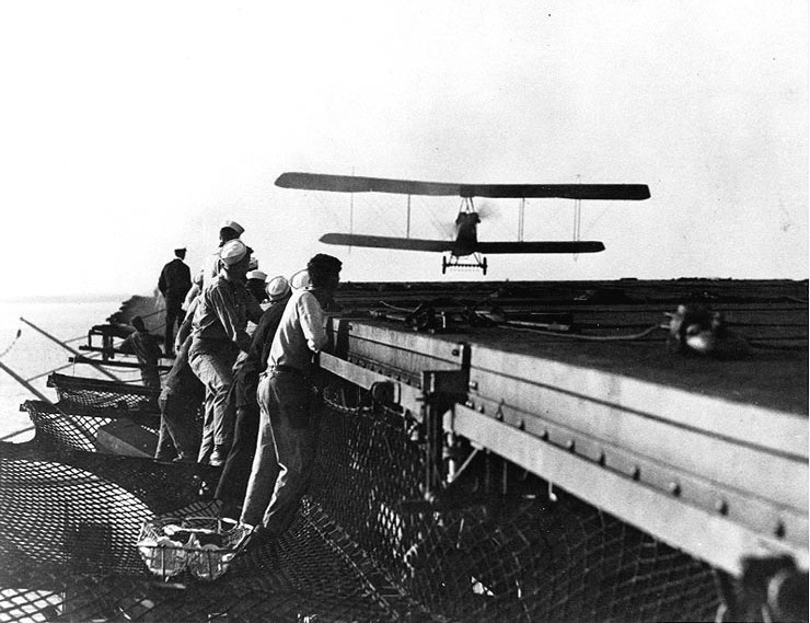 An Aeromarine 39B piloted by Chevalier is seen just before it touches down on the flight deck of USS Langley (CV-1) on 26 October 1922 – the first landing aboard an American aircraft carrier. Via National Naval Aviation Museum.