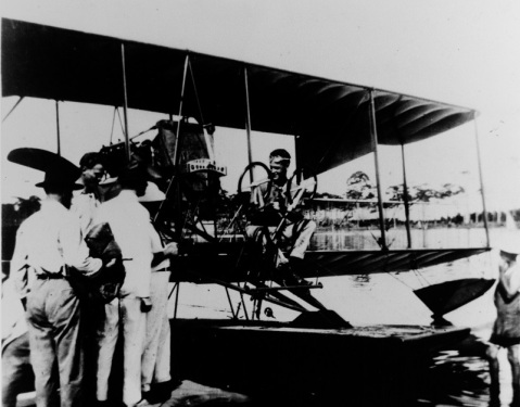 """Godfrey """"Darb"""" de Courcelles Chevalier, Naval Aviator No. 7, in the pilot's seat of early aircraft at Perdido Beach, Alabama, circa 1914. Hunter Brown is his passenger (may be seen bareheaded at intersection of engine block and propeller), and Charles W. Virgin (in bathing suit) is at right. NH 70285"""