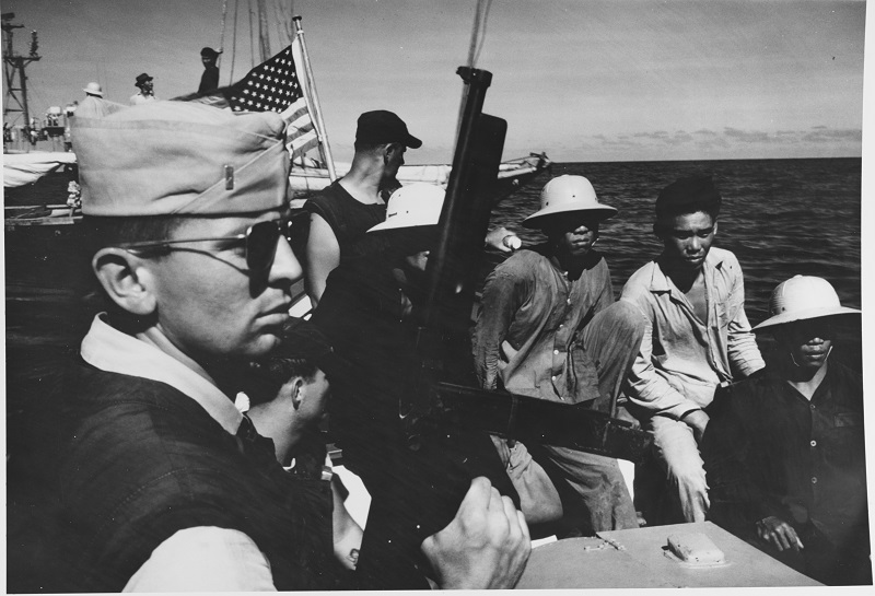 Tommy guns, aviators and khakis! Ensign Caldwell of Houlton, Maine, stands guard in a motor whaleboat with a .45 caliber submachine gun M1928AL (it is actually an M1A1) off the coast of South Vietnam. The Vietnamese men wait as their junk is searched by USS FORSTER (DER-334) crewmembers, 15 April 1966. Catalog #: K-31208. Copyright Owner: National Archives Original Creator: Photographer, Chief Journalist Robert D. Moeser