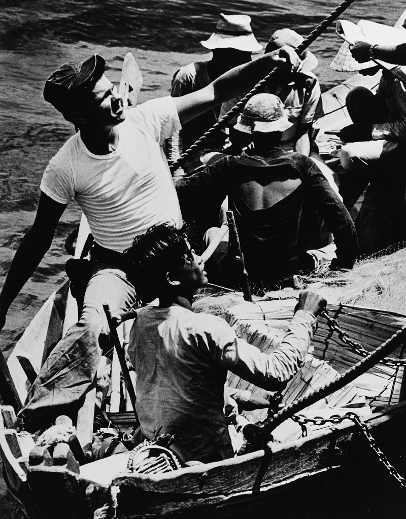 Men check a sampan for contraband cargo. The chain is to be passed under the sampan's hull to detect cargo that might be hidden below the waterline. South China Sea, March 1966. Catalog #: USN 1142219