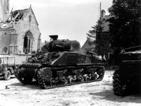 A pair of burnt out Canadian M4A2 Shermans of the 10th Armored Regiment (The Fort Garry Horse) at the foot of the church at Rots – June 1944