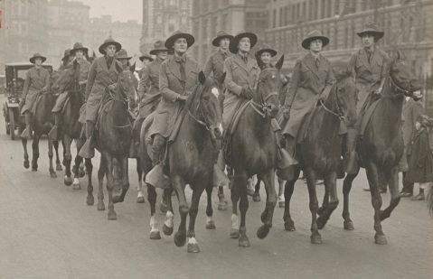 Original Caption: New York's female cavalry drilling in city streets. The American Woman's League for Self Defense who have organized a cavalry troop, started outdoor drilling in the streets adjacent to the 1st Field Artillery at 67th St. & Broadway, New York, where their first lessons were received under the supervision of army officers. Photo shows Captain Ethel Schiess giving orders to the troop. Photographer: Western Newspaper Union
