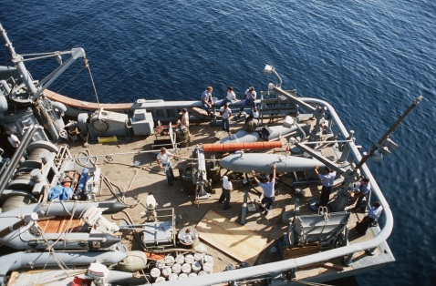 Crewmen handle a minesweeping float on the stern of the ocean minesweeper USS INFLICIT (MSO 456), 4/27/1988