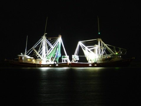 Two 65-foot shrimp boats, F/V Dustin II and F/V St. Peter just feet off Deer Island with stern to stern with their working lights on.