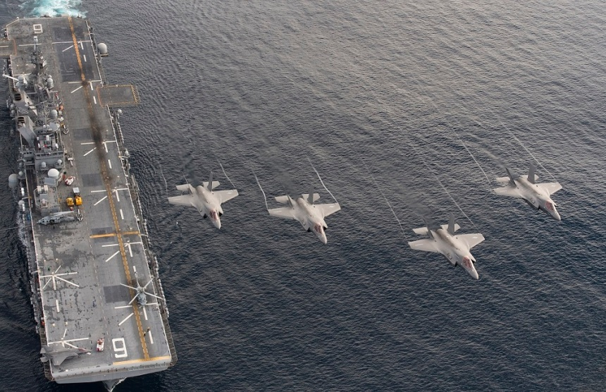 161120-N-VT045-0001 PACIFIC OCEAN (Nov. 19, 2016) Four F-35B Lightning II aircraft perform a flyover above the amphibious assault ship USS America (LHA 6) during the Lightning Carrier Proof of Concept Demonstration.  The F-35B will eventually replace three  Marine Corps aircraft; the AV-8B Harrier, F/A-18 Hornet and the EA-6B Prowler. (U.S. Navy photo by Andy Wolfe/Released)