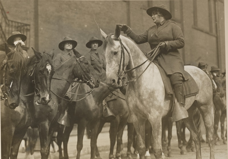 Original Caption: Cavalry corps of the American Women's League for Self Defense. Cavalry Corps of the American Woman's League for Self Defense held its first public drill in the 1st Field Artillery Armory, Broadway and 60th Street, New York. Miss Ethel May Schiess, who is seen in the front, put the 20 prospective scouts and message bearers through their paces, while the 1st Field Artillery band played. Photographer: Kadel and Herbert