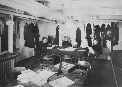 Junior officers reading by electric light, in the ship's steerage quarters, 1888. Note objects on the table in the foreground, among them a T-Square and other drafting instruments, pipes and cigarettes, and dice. U.S. Naval History and Heritage Command Photograph. Catalog #: NH 47025