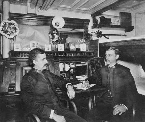 Two of the ship's warrant officers in their stateroom, 1888. Note personal photographs and other decorations in the room, fancy wooden desk, and uniform collar insignia worn by these officers. U.S. Naval History and Heritage Command Photograph. Catalog #: NH 52424