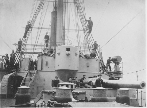 View on the forecastle, looking aft, with crewmembers at their stations looking out for torpedo attack, 1888. Several weapons and related items are visible on the bridge wings, all of relevance for repelling a torpedo boat attack. They include (from left to right): a 1-pounder gun, a Gatling machine gun, a 37mm revolving cannon, and a searchlight. The ship's forward 8/30 gun is in the right foreground, with its crew standing at their posts. U.S. Naval History and Heritage Command Photograph. Catalog #: NH 56537