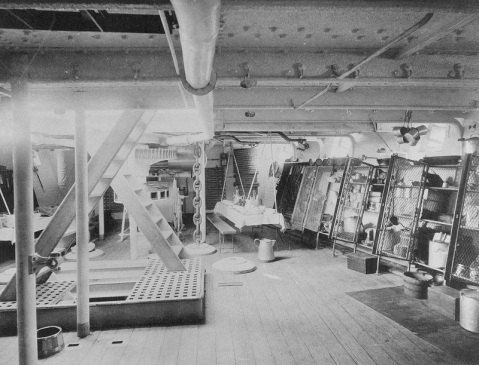 View in the forward compartment of the berth deck, looking toward the bow, 1888. Note the storage lockers at right, tin cups hanging from the overhead, swinging mess table, cable reel, anchor chain and capstain mechanism, ladders and hatches. U.S. Naval History and Heritage Command Photograph. Catalog #: NH 56539