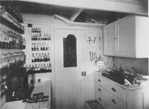View in ship's dispensary, 1888, showing bottles in sheet metal wall racks; instruments on tables and bulkheads; wooden joinerwork; electric light with hanging hook on top; and use of overhead pipes as a storage rack. U.S. Naval History and Heritage Command Photograph. Catalog #: NH 56543