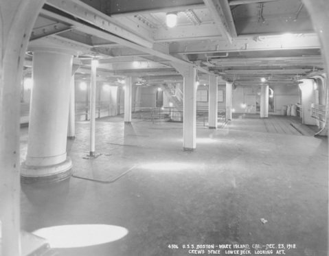 View in the crew's space, on the lower deck looking aft, with the mainmast at left. Taken at the Mare Island Navy Yard, California, 23 December 1918, following Boston's conversion for service as the receiving ship at Yerba Buena Island, California. Note the electric lights in the overhead. U.S. Naval History and Heritage Command Photograph. Catalog #: NH 74472