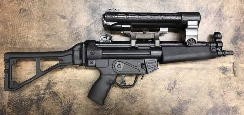 old-school-hk-optic-made-by-hensoldt-that-projects-light-with-a-crosshair-in-the-beam-it-runs-on-5-c-batteries-and-weighs-as-much-as-the-mp5-itself