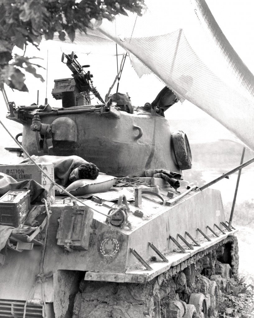 Trooper Andy Parenteau of the Lord Strathcona's Horse (Royal Canadians) sleeps on the back of a Canadian Sherman M4A3(76)W HVSS tank, Korea. Note the American ration box and United Nations/Canada crest on the tail