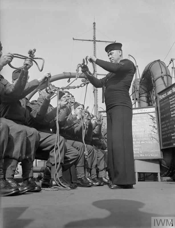 """Britain's sea soldiers in training. Men of the Maritime Royal Artillery are now being given elementary training in seamanship at HMS PRESIDENT, the DEMS base on the Thames. Here a number of men are being initiated into the mysteries of """"Bends and Hitches"""" (knots) by Leading Seaman W J Bateman, Enfield, Middlesex. Copyright: © IWM. Original Source: http://www.iwm.org.uk/collections/item/object/205149660"""
