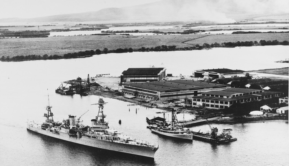 Heavy cruiser USS Augusta (CA-31) steaming past the Fleet Air Base at Pearl Harbor, T.H., January 1933. USS AVOCET (AM-19), serving as an aircraft tender, is at the dock. Note cane fields being burned at upper right. Catalog #: 80-CF-21338-4