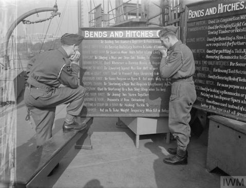 Learning the ropes. Two of the members of the Maritime Royal Artillery study the information board describing how to form bends and hitches. IWM A 16786. Copyright: © IWM. Original Source: http://www.iwm.org.uk/collections/item/object/205149661