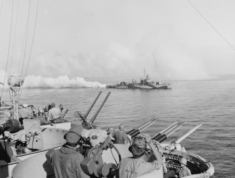 USS Cony (DD-508) lays a smoke screen near USS West Virginia (BB-48), to protect shipping off Leyte from Japanese air attack, during the landings there on 20 October 1944. Note manned anti-aircraft batteries on board the battleship, including a Mark 51 director in the foreground, 20mm gun at left, 40mm quad gun mount in center and 5/38 twin gun mounts beyond. Official U.S. Navy Photograph, now in the collections of the National Archives. Catalog #: 80-G-289679