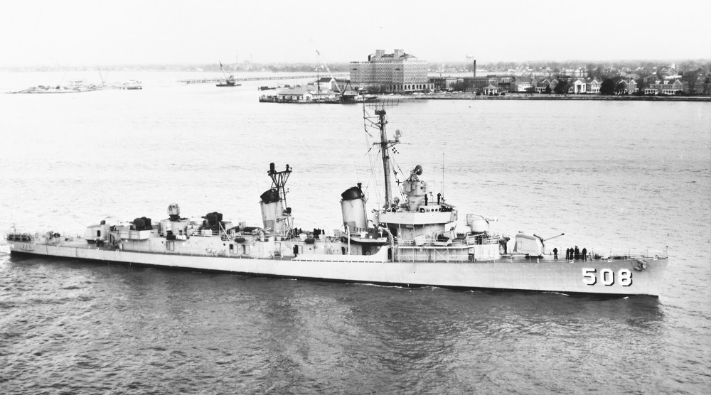 (DDE-508) In Hampton Roads, Virginia, 12 March 1957. Old Point Comfort, with the Chamberlain Hotel and Fort Monroe, is in the center and right background. Note bridge-tunnel construction work in the left background. Official U.S. Navy Photograph, from the collections of the Naval History and Heritage Command. NH 104882