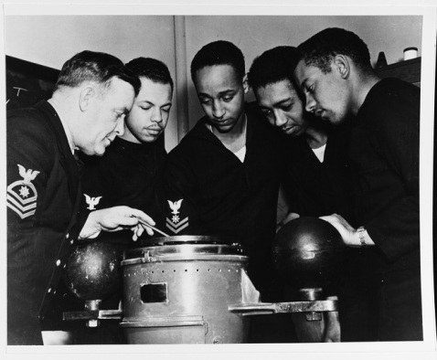 Quartermasters receive compass instruction, during training for Mason's crew at the Norfolk Naval Training Station, Virginia, 3 January 1944. The instructor is QMC L.J. Russell, USNR (left). Trainees are (left to right): QM2c Charles W. Divers, QM2c Royal H. Gooden, QM2c Calvin Bell, QM3c Lewis F. Blanton. Official U.S. Navy Photograph, now in the collections of the National Archives. 80-G-214542