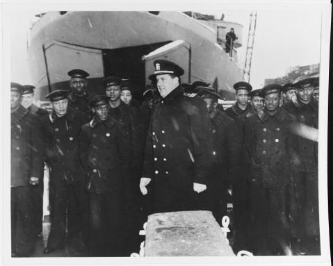 Commissioning ceremonies on the ship's fantail, held in a driving snowstorm at the Boston Navy Yard, Massachusetts, 20 March 1944. Her Commanding Officer, Lieutenant Commander William M. Blackford, USNR, is in the center with some of the crew standing in ranks behind him. Ship in the background is an LST, with bow doors partially opened. Official U.S. Navy Photograph, now in the Collections of the National Archives. Catalog #: 80-G-218856