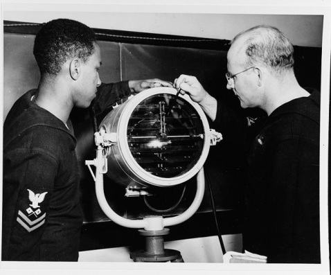 Signalman 1st Class Ernest V. Alderman, USNR, (right) explains various parts of a signal lamp to SM2c Julius Holmes, during training for Mason's crew at Norfolk Naval Training Station, Virginia, 3 January 1944. Official U.S. Navy Photograph, now in the collections of the National Archives. Catalog #: 80-G-44827