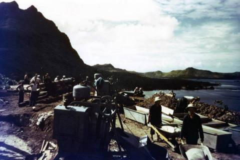 "Seabees placing a Navy 7""/45 Gun on a hill overlooking Teavanui Harbor, circa February 1942. The town of Vaitape is on the point of land at right. National Archives photograph, 80-G-K-1125 (Color)."