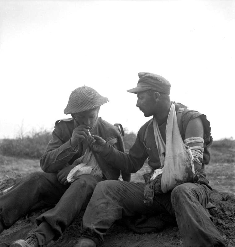A wounded German POW of the 15th Panzergrenadier Division offers a light to one of his captors; a wounded British Army soldier of the 6th Durham Light Infantry, 50th Infantry Division, XXX Corps. March 23rd, 1943