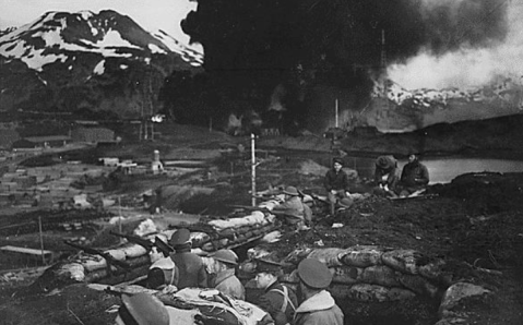 "Japanese attack on Dutch Harbor, June 3, 1942. Group of Marines on the ""alert"" between attacks. Smoke from burning fuel tanks in background had been set afire by a dive bomber the previous day. Alaska. NARA 520589"
