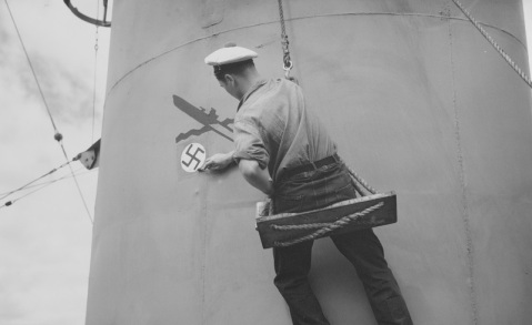 Sénégalais (French Escort Ship, formerly USS Corbesier, DE-106) French sailor paints a submarine kill symbol on the ship's smokestack, following the sinking of German submarine U-371 off the Algerian coast on 4 May 1944. During the action, Sénégalais delivered the final attack on U-371, but was herself torpedoed and damaged. Official U.S. Navy Photograph, now in the collections of the National Archives. Catalog #: 80-G-K-1606