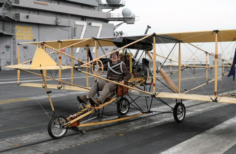 Retired Navy Cmdr. Bob Coolbaugh sits in the pilot seat of a replica Curtiss Hudson Flier biplane, the first aircraft to launch from the deck of a navy ship, Nov. 15, 2010, on the flight deck of USS George H.W. Bush (CVN 77) while in port in Norfolk, Va. The replica was built as part of celebrations for the Centennial of Naval Aviation. (DoD photo 101115-N-3885H-265 by Mass Communication Specialist 3rd Class Nicholas Hall, U.S. Navy/Released)