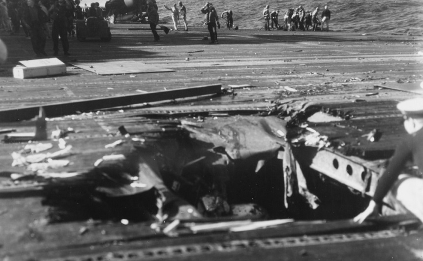 Bomb hole in flight deck from dropped by a Kamikaze plane that hit the ship's forward elevator, off Formosa, 21 January 1945. Crewmen in the background are cleaning up debris from the hit. 80-G-273223