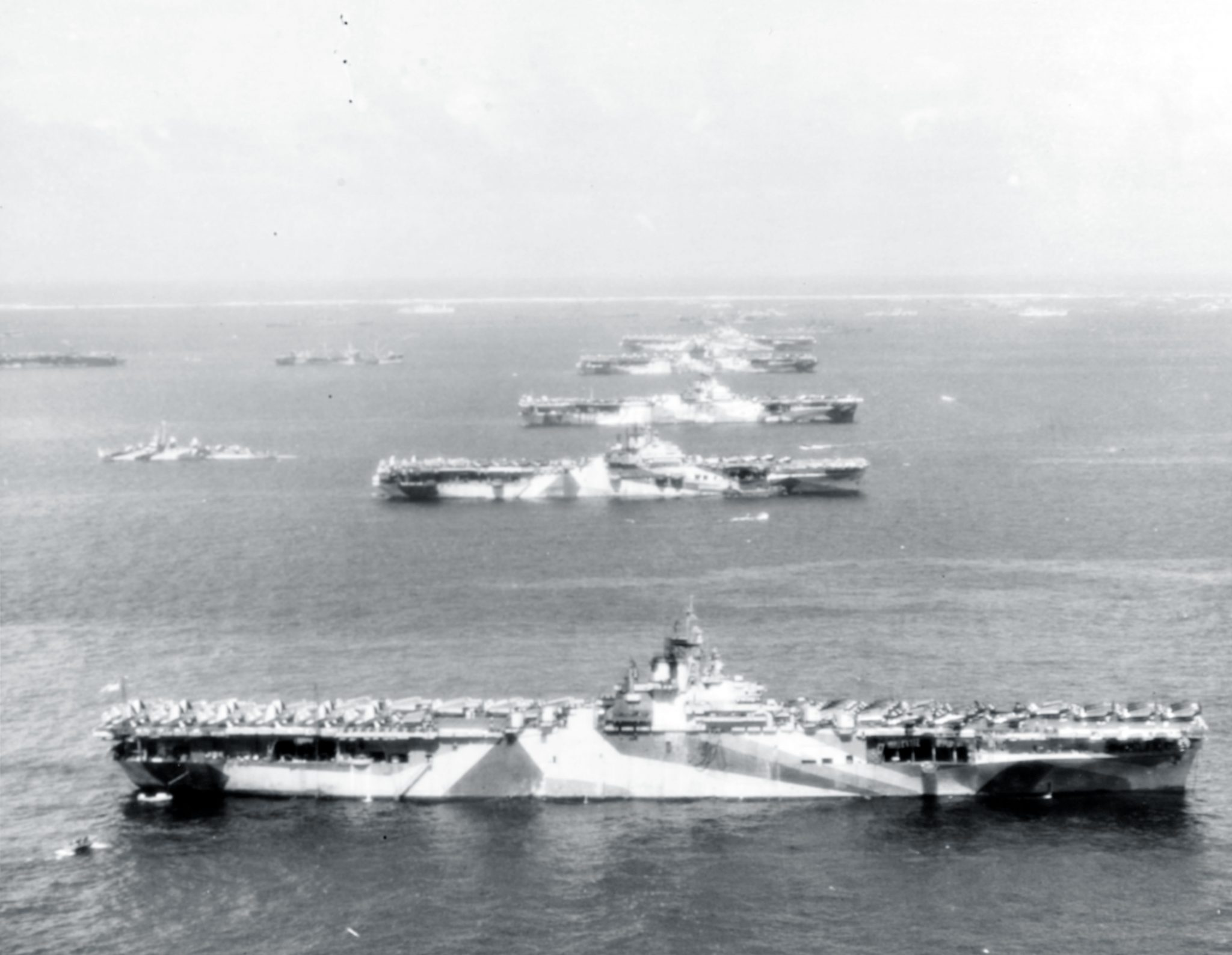 """""""Murderers' Row"""" Third Fleet aircraft carriers at anchor in Ulithi Atoll, 8 December 1944, during a break from operations in the Philippines area. The carriers are (from front to back): USS Wasp (CV-18), USS Yorktown (CV-10), USS Hornet (CV-12), USS Hancock (CV-19) and USS Ticonderoga (CV-14). Wasp, Yorktown, and Ticonderoga are all painted in camouflage Measure 33, Design 10a. Photographed from a USS Ticonderoga plane. 80-G-294131"""