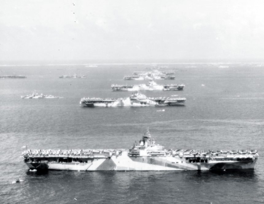 """Murderers' Row"" Third Fleet aircraft carriers at anchor in Ulithi Atoll, 8 December 1944, during a break from operations in the Philippines area. The carriers are (from front to back): USS Wasp (CV-18), USS Yorktown (CV-10), USS Hornet (CV-12), USS Hancock (CV-19) and USS Ticonderoga (CV-14). Wasp, Yorktown, and Ticonderoga are all painted in camouflage Measure 33, Design 10a. Photographed from a USS Ticonderoga plane. 80-G-294131"