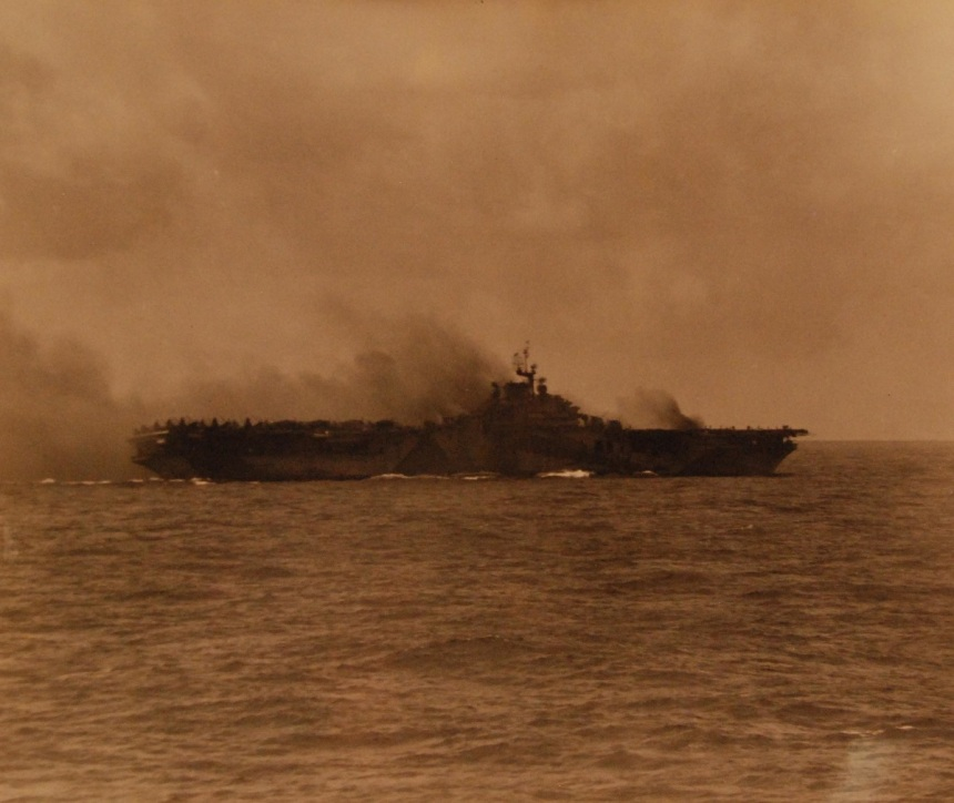 USS Ticonderoga (CV 14) afire after a bomb hit by Japanese suicide plane at Okinawa in the Ryukyu Islands. As seen from USS Vincennes (CL 14), 21 January 1945. 80-G-343576