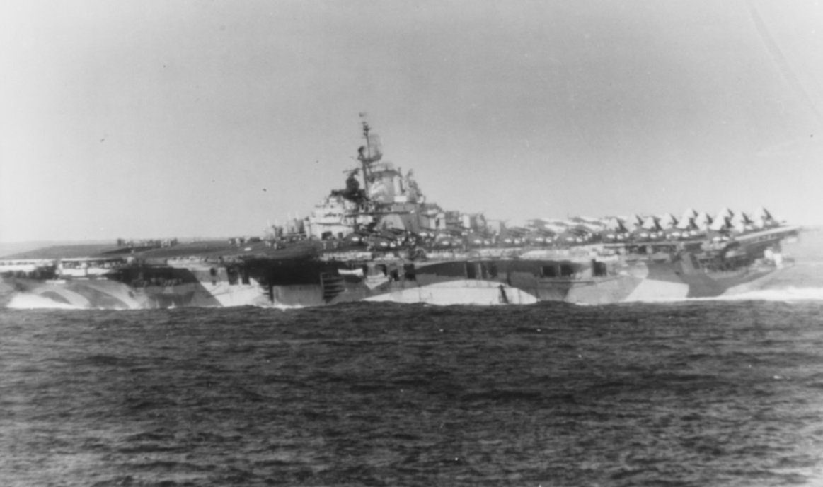 """Ticonderoga Underway with """"all fires out"""", after being hit twice by Kamikazes of Formosa, 21 January 1945. Note: fire damage to her island. Photographed from USS ESSEX (CV-9) #: 80-G-373726"""