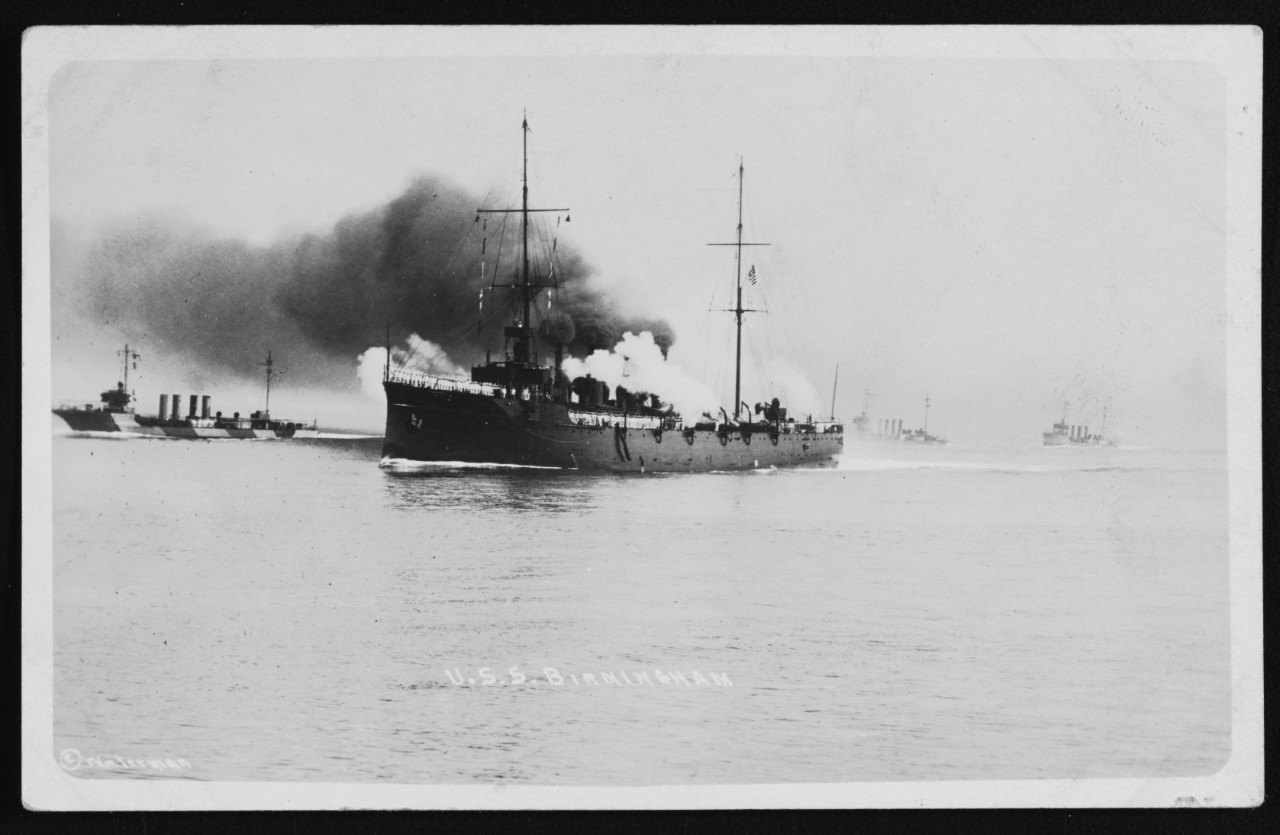 USS Birmingham Firing salutes with her crew manning the rails, accompanied by three 750-ton type destroyers. Photographed by Waterman. Birmingham's black paint scheme and structural details, and the white uniforms worn by her crew, indicate that the date of this photograph is mid-1916, when Birmingham was flagship of the Atlantic Fleet's Destroyer Force. Location may well be near Hampton, Virginia, base of Waterman family's photographic business. Note what appears to be pattern camouflage (perhaps an experimental scheme) worn by the destroyer on the left. Donation of Charles R. Haberlein Jr., 2007. NH 105382