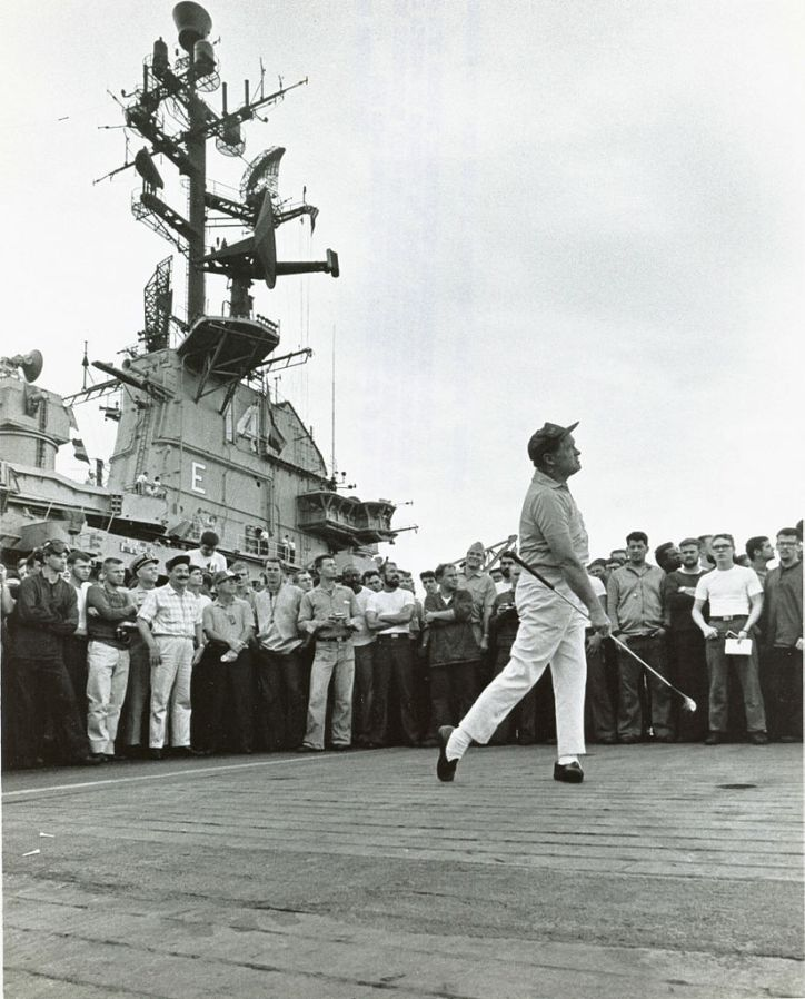Entertainer Bob Hope tees-off on the flight deck aboard the U.S. Navy aircraft carrier USS Ticonderoga (CVA-14) during his visit to the carrier off the coast of Vietnam on 26 December 1965. USN Photo 030728-N-0000X-001