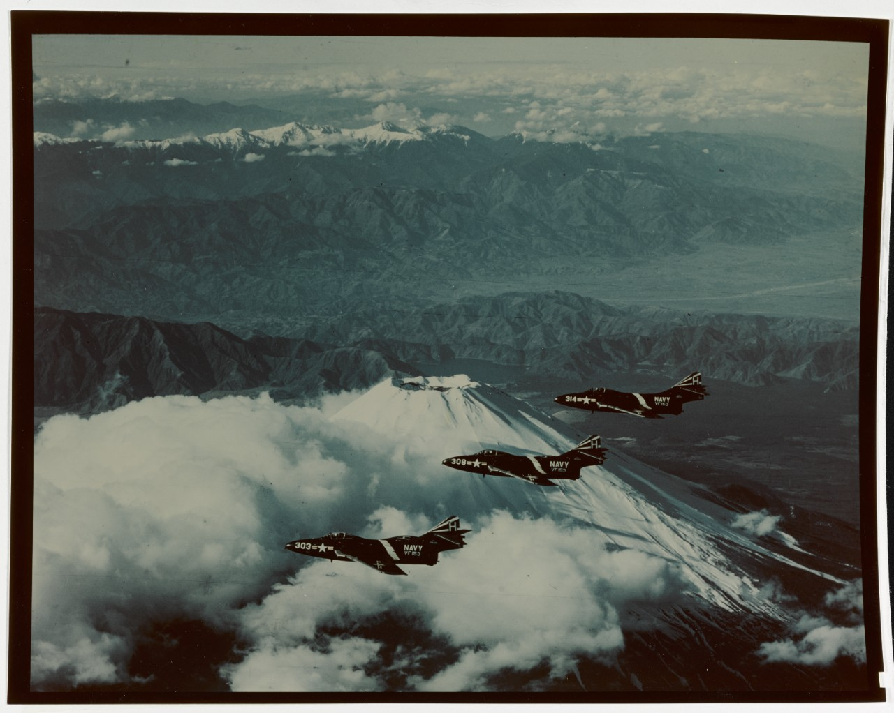 Grumman F9F-6 Cougar Jet Fighters Fly in formation over Mount Fuji, Japan, 12 December 1954. They are from USS YORKTOWN's (CVA-10), VF -153. Plane in foreground is BU 128209. 80-G-K- 17821