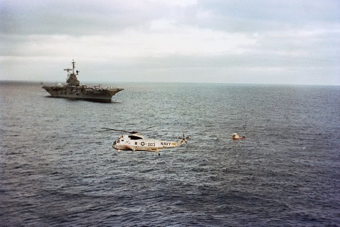 22 June 1973 The Skylab 2 Command Module, with astronauts Charles Conrad Jr., Joseph P. Kerwin and Paul J. Weitz still inside, floats in the Pacific Ocean following successful splashdown about 835 miles southwest of San Diego, California. The prime recovery ship, USS Ticonderoga, approaches from the left background. A recovery helicopter hovers in the foreground. The three Skylab 2 crewmen had just completed a 28-day stay with the Skylab 1 space station in Earth orbit conducting numerous medical, scientific and technological experiments. NASA Photo S73-29147
