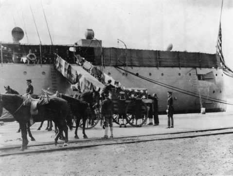 The flag-draped caskets of the victims of the USS Maine explosion are brought ashore at the Washington Navy Yard, District of Columbia, from USS Birmingham (Scout Cruiser # 2), 23 March 1912. Of the 66 sets of remains only one was identified and returned to his home town the rest were reburied at Arlington Cemetery. NH 1690
