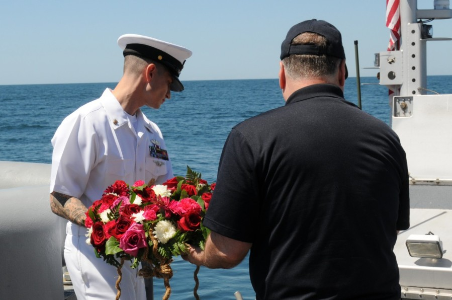 Retired Rear Admiral Samuel Cox, Director, Naval History and Heritage Command, speaks to Sailors aboard the USNS Grasp (T-ARS-51) during a wreath-laying ceremony to commemorate the 100th anniversary of the sinking of the USS San Diego (ACR 6).