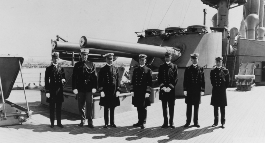 """Admiral William B. Caperton, USN Commander-in-Chief, U.S. Pacific Fleet (center) With members of his staff on board USS San Diego (Armored Cruiser No. 6) at San Diego, California, circa 1916-17. The ship's after 8""""/45 twin gun turret is behind them. Those present are (from left to right): Lieutenant (Junior Grade) H.M. Lammers, USN; Captain R.M. Cutts, USMC; Medical Inspector E.S. Bogert, USN; Admiral Caperton; Pay Inspector J. Fyffe, USN; Lieutenant A.T. Beauregard, USN; and Paymaster C.S. Baker, USN. Courtesy of the Naval Historical Foundation. Collection of Adm. W.B. Caperton. NH 83793"""