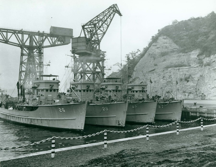 Four U.S. Navy minesweepers (AMS) tied up at Yokosuka, Japan, following mine clearance activities off Korea. Original photo is dated 30 November 1950. These four ships, all units of Mine Division 31, are (from left to right): USS Merganser (AMS-26); USS Osprey (AMS-28); USS Chatterer (AMS-40) and USS Mockingbird (AMS-27). Ship in the extreme left background is USS Wantuck (APD-125). Official U.S. Navy Photograph 80-G-424597, now in the collections of the National Archives.