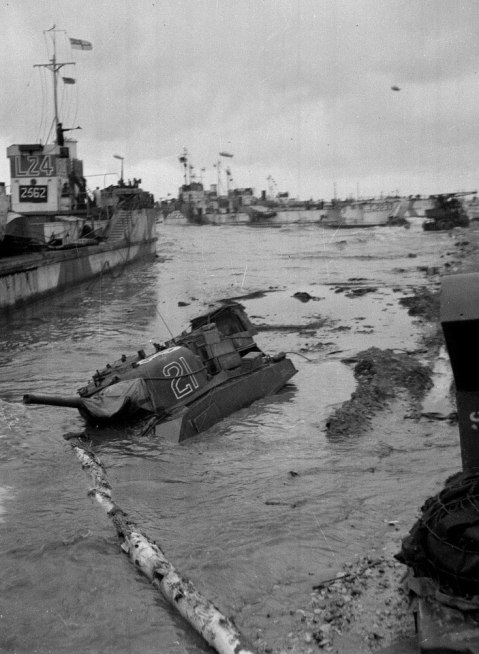 Assault craft and a partially submerged Sherman tank during the initial stages of the invasion of Normandy, June 1944. Photograph by Major Wilfred Herbert James Sale, MC, 3rd/4th County of London Yeomanry (Sharpshooters), World War Two, North West Europe, 1944. Although Allied intelligence had identified which areas of beach were suitable for the landing of vehicles, several tanks, jeeps and lorries were lost in water that was deeper than expected or in the shifting sands. The Normandy invasion beaches were also choked with disabled and sunken landing vessels which made unloading vehicles even more hazardous. NAM. 1975-03-63-18-33