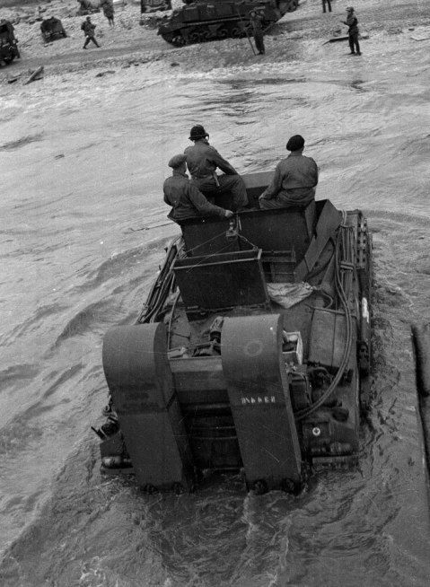 An ARV (Armoured Recovery Vehicle) wading ashore in Normandy, 7 June 1944. Photograph by Major Wilfred Herbert James Sale, 3rd/4th County of London Yeomanry (Sharpshooters), World War Two, North West Europe, 1944. 3rd County of London Yeomanry (Sharpshooters) landed on 7 June 1944 in support of 153rd Brigade near Mont Fleury La Rivière. The ARV shown is a Sherman ARV 1 with deep wading trunking applied to protect exhausts as well as crew and engine compartments from sea water. These devices would have been discarded once ashore. NAM. 1975-03-63-18-28