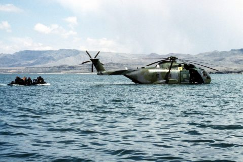 A CH-3E Sea King helicopter from the 1550th Combat Crew Training WIng floats on the surface of Elephant Butte Lake as members of a Navy sea-air-land (SEAL) team approach in an inflatable boat during the joint Air Force/Navy special operations exercise Chili Flag '90.