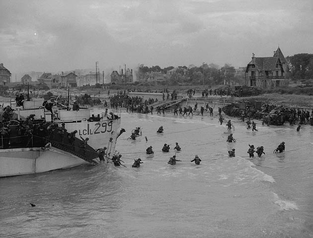 """looking east along the """"Nan White"""" beach, showing personnel of the 9th Canadian Infantry Brigade landing on D-Day"""