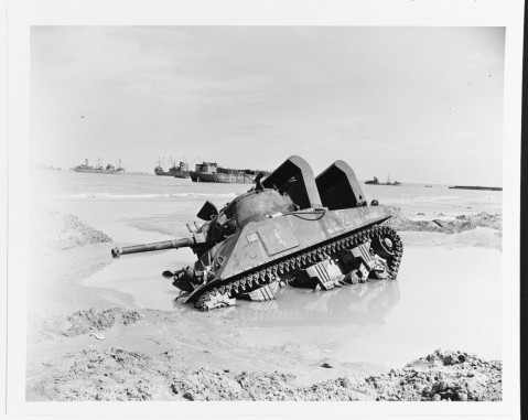 Mired M4 Sherman tank on a Normandy invasion beach, 12 June 1944. name Cannon Ball, is fitted with raised air intakes for amphibious use 80-G-252802
